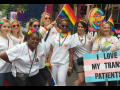"""Nurses in white scrubs with rainbow flags and accessories; one carries a sign """"I Love My Trans Patients"""" with the trans flag (pastel blue, pink, and white stripes)"""