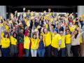NewsGuild members standing together in yellow, smiling holding signs with arms up