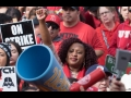 Black woman raising her fist in a crowd of strikers