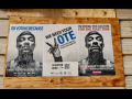 "On a boarded up section of a brick wall, three posters. The outer two show Snoop Dogg's face, and the middle one shows a hand making a ""V"" gesture. Text of the 3 posters: 1. ""I'm voting because I want to end police brutality."" 2. ""We need your vote. Black lives matter. Black votes matter. Register here. [QR code.]"" 3. ""I'm voting this election for the first time because I can't stand to see that punk in office another year."""