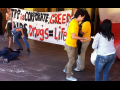 """Activists draw chaik outlines on the ground in front of a hotel entrance; one outline is labeled """"Vietnam."""" Others hold a banner: """"TPP is corporate greed. AiDS drugs = life."""""""