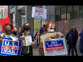 "Picketers (Black and white, men and women) marching in front of a post office. Signs say ""U.S. Mail Is Not for Sale,"" ""Postmaster DeJoy Is Destroying Our Post Office,"" ""Save Our Public Postal Service: Forever Essential."" Also visible are copies of the flyer ""Dump DeJoy and His 10-Year Plan."""