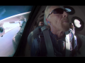 Screenshot of Richard Branson, wearing sunglasses and earphones, in a rocket. Two other crew members are visible behind him. On the left is a window through which you can see part of the outside of the rocket, labeled VIRGIN, and blue sky.