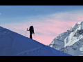Silhouette of a skier ascending a mountain slope with pink sky in background