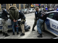 Outdoors, four police officers handcuffing two people against two police cars