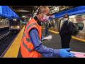 Man in orange vest hands out masks inside a train station