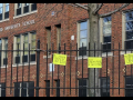 "handwritten signs ""we miss you"" hang on the fence outside a brick building labeled Hartford University School"
