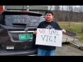 protester for VSCS Thrive! with a sign and his car that has a pro-VTU slogan on the back windshield