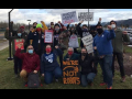 """A group of Amazon solidarity activists pose for a photo with their fist raised. Some hold signs that read """"Put Workers First,"""" """"Amazon Workers Need a Union,"""" and """"Solidarity Forever."""""""