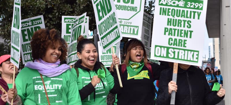 Four women carrying picket signs for AFSCME 3299 strike