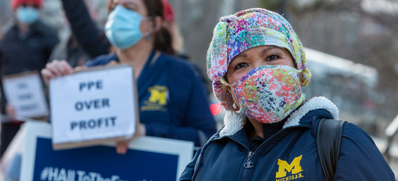 "Health care workers outdoors in U of Michigan Medical Center coats. Person in front wears a colorful mask and smiles right into the camera. Behind, person holds signs ""PPE OVER PROFIT"" and ""#HAILToTheFrontLine"""