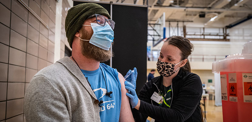 Woman on right in mask administering covid vaccine to man in mask and hat on left.