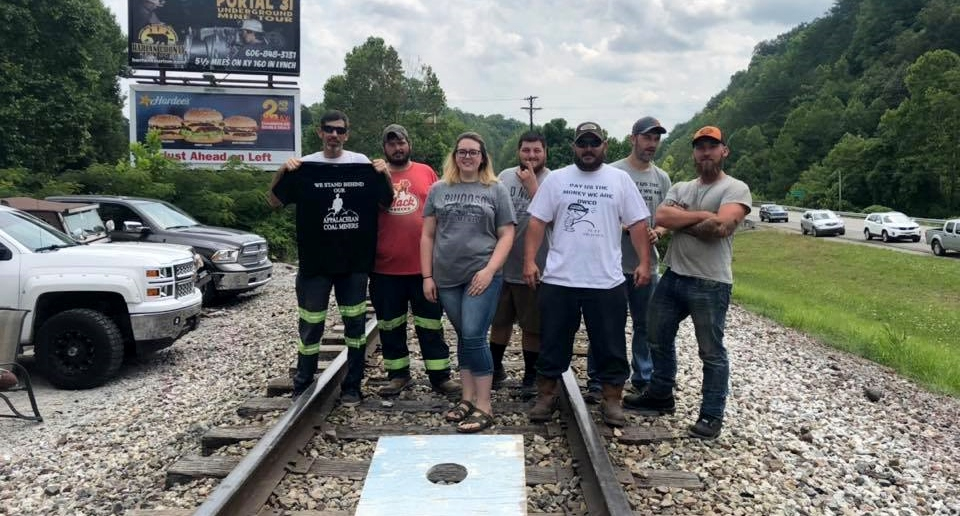 """Five people stand on railroad tracks, with a cornhole game at their feet. Some wear """"pay us what we are owed"""" shirts."""