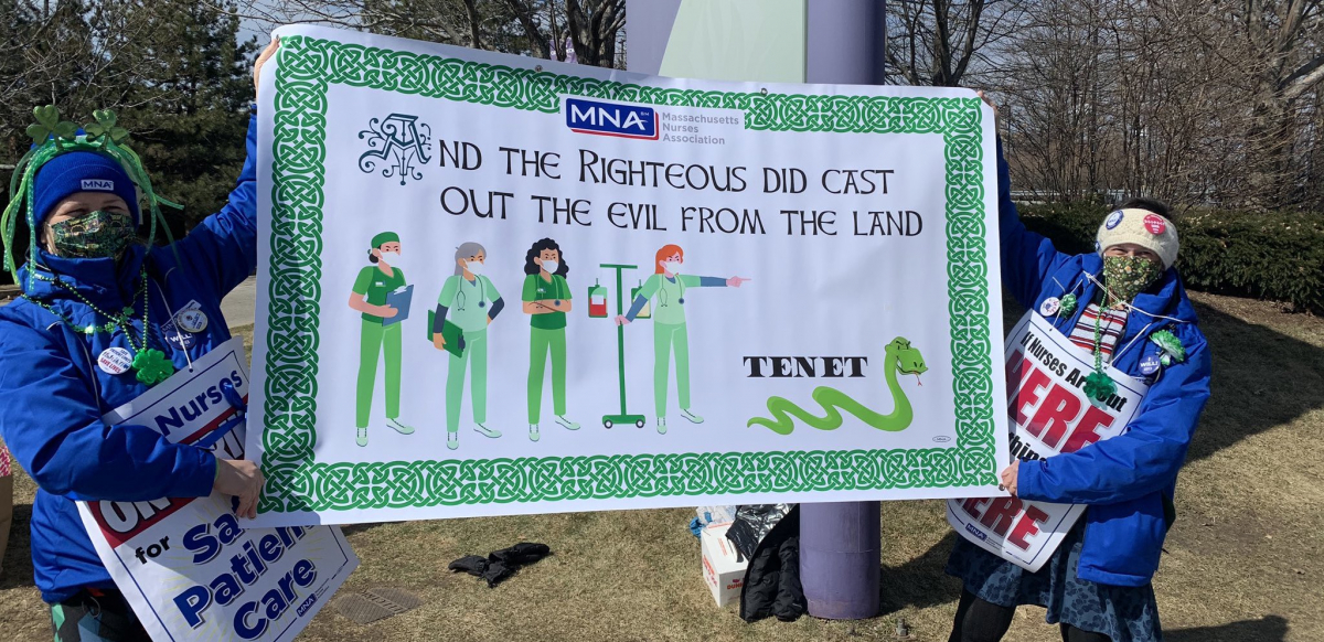 """Two nurses hold a green St. Patrick's Day banner that reads """"And the righteous did cast out the evil from the land."""" The banner pictures a group of nurses chasing off a snake labeled Tenet."""