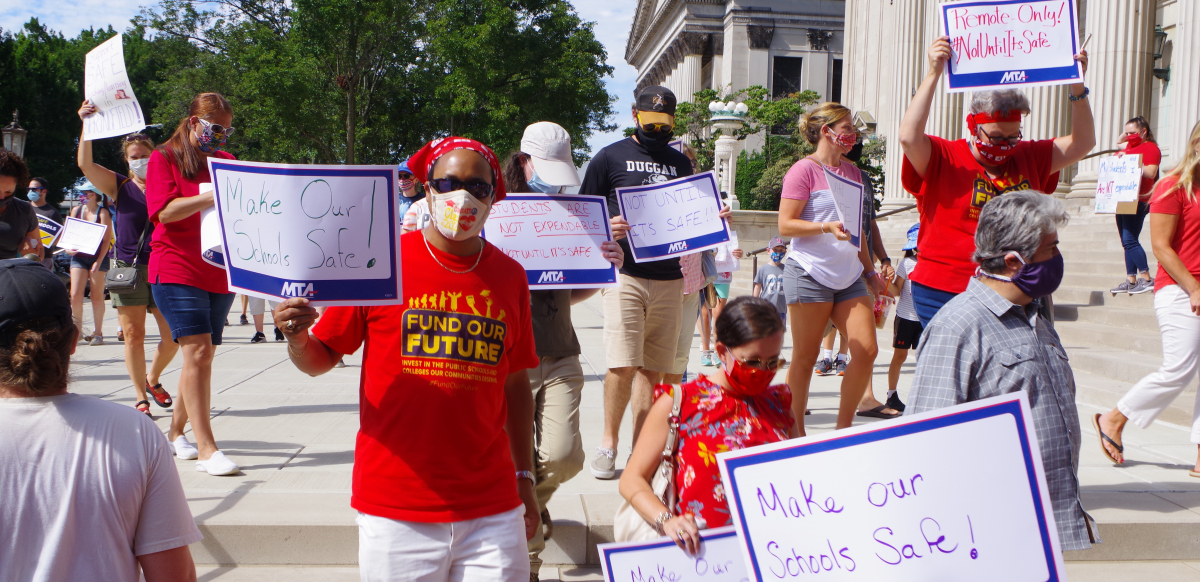 Teachers wearing masks hold signs that say Make Our Schools Safe and Not Until It's Safe.