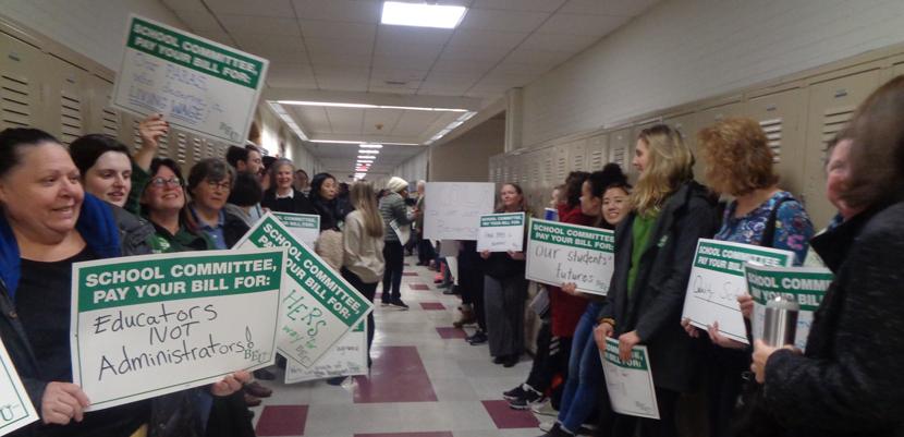 Brookline paraeducators with signs lining hallway of school.