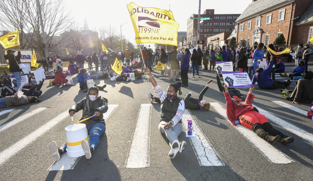 "Several women sit in the middle of the crosswalk, holding upside-down buckets that they are using as drums. One holds a flag that reads ""SEIU 1199 New England: Health Care for All."""