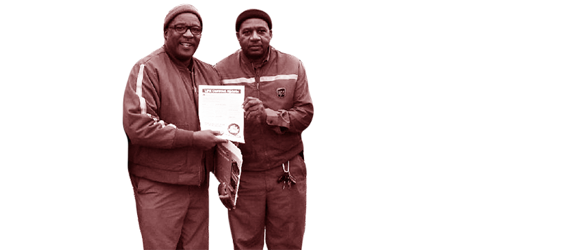 Two UPS workers holding a document.