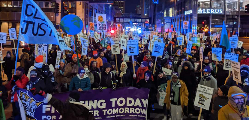 Crowd of climate strikers at night with signs and flags and a banner in downtown Minneapolis.