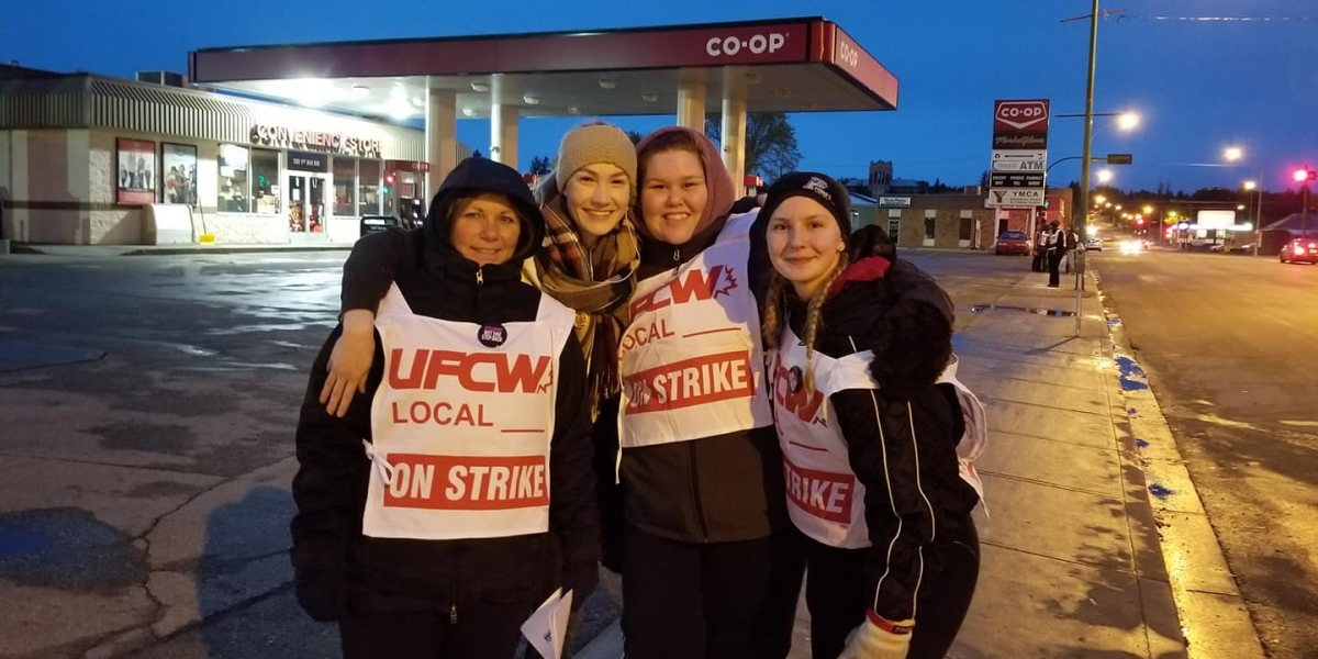 "Four smiling women wearing ""UFCW Local ON STRIKE"" signs stand in front of a Co-op gas station, arms around each other's shoulders"