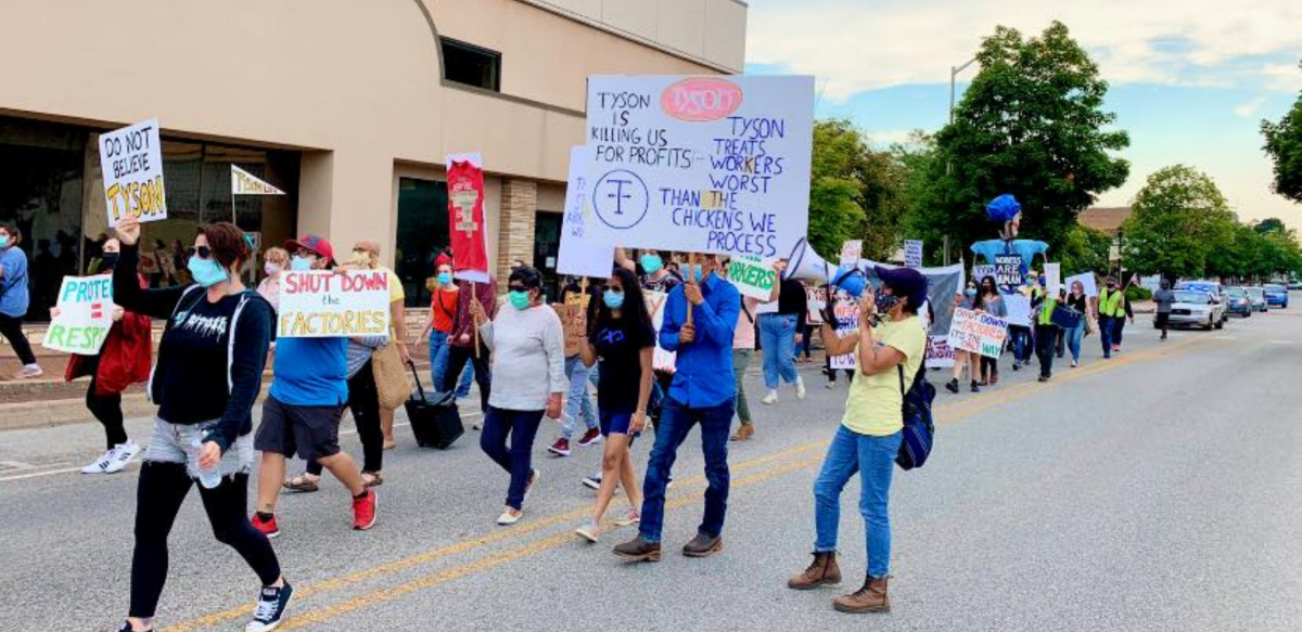 """Masked people march with signs: """"Tyson Is Killing Us for Profits. Tyson Treats the Workers Worst than the Chickens We Process."""" """"Don't Believe Tyson."""" """"Shut Down the Factories."""" """"Protect = Respect."""""""