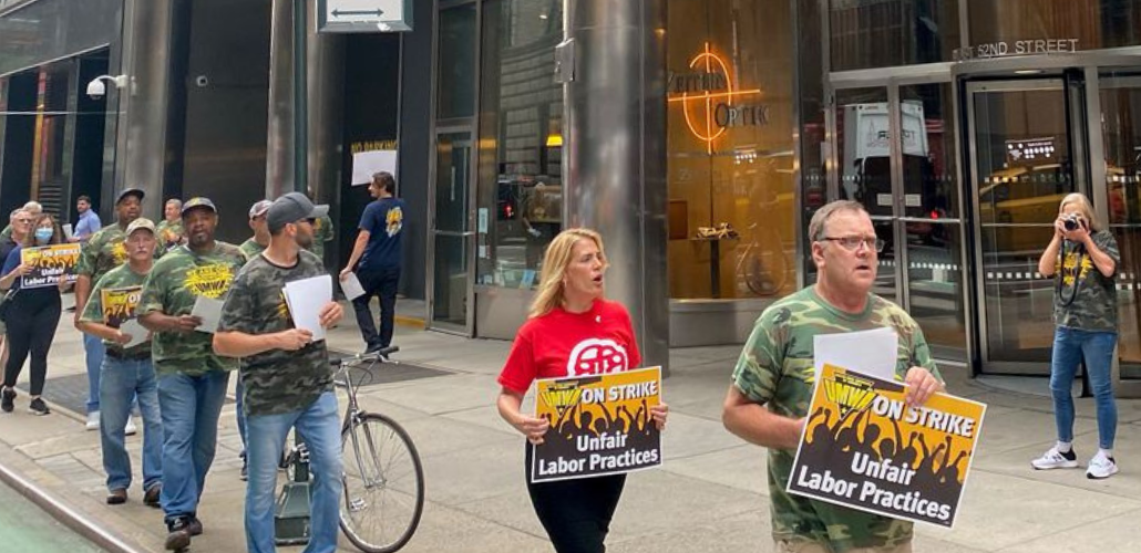"""Picketers march outside an office building, most in camouflage shirts. They carry signs: """"UMWA ON STRIKE: Unfair Labor Practices"""""""