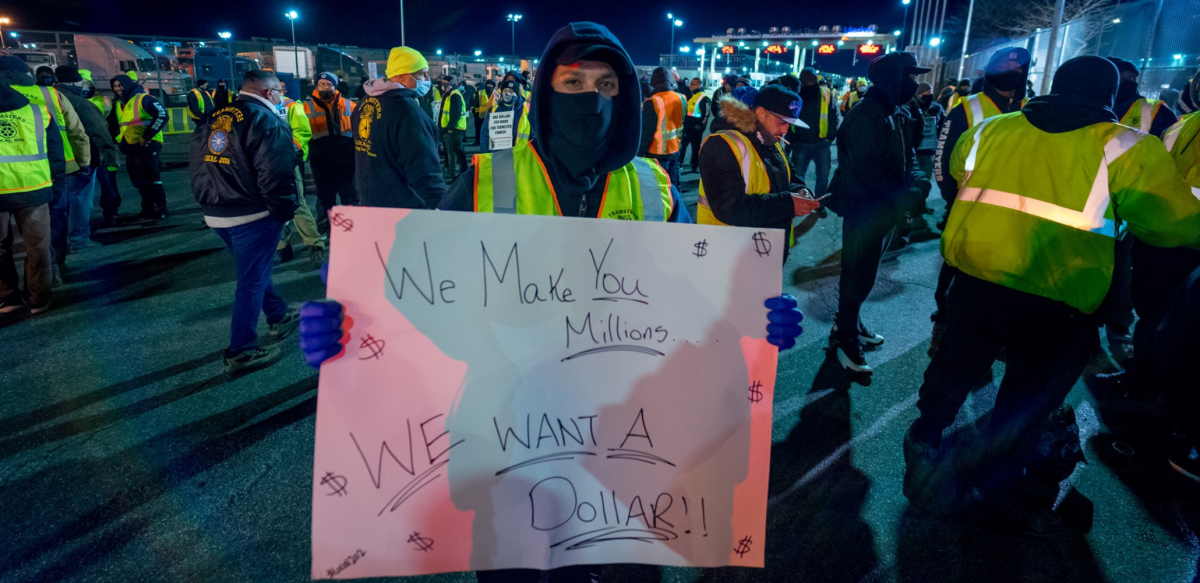"Person in yellow vest at night, outdoors in crowd, holds handwritten sign: ""We make you millions, we want a dollar!"""
