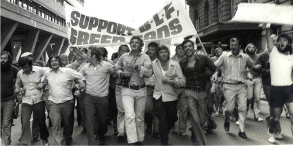 """Black and white photo of men marching with a banner: """"SUPPORT BLF GREEN BANS"""""""