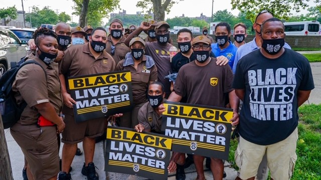 """crowd of workers, many in brown UPS uniforms, with """"Black Lives Matter"""" signs"""