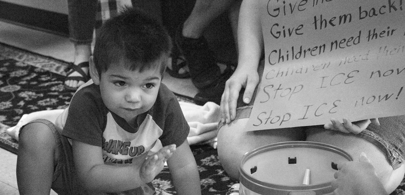 Child crouched in front of toys and a sign against ICE