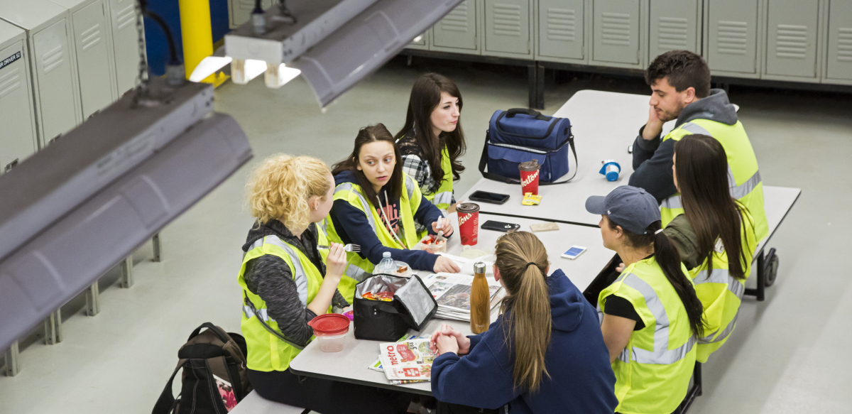 Workers in yellow vests sit around a lunch table at work.
