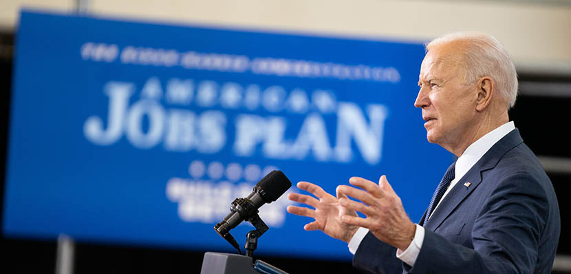 sideview of President Joe Biden speaking at a podium at Pittsburgh Carpenters Hall on March 31, 2021, with American Jobs Plan sign in background (white on blue)