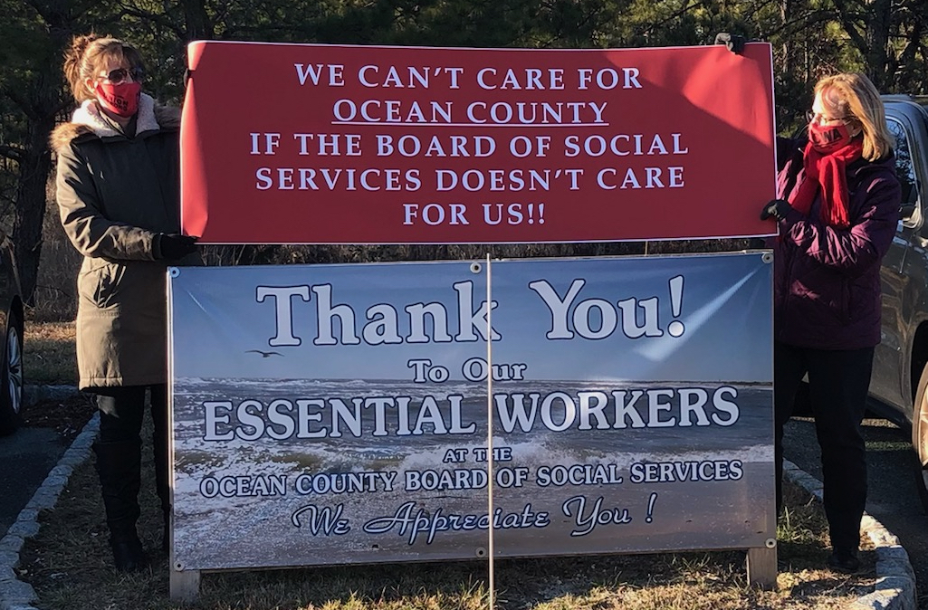 """Two workers hold a banner reading """"We Can't Care for Ocean County If the Board of Social Services Doesn't Care About Us!"""" over the """"Thank You to Our Essential Workers"""" sign that the Board had put up."""