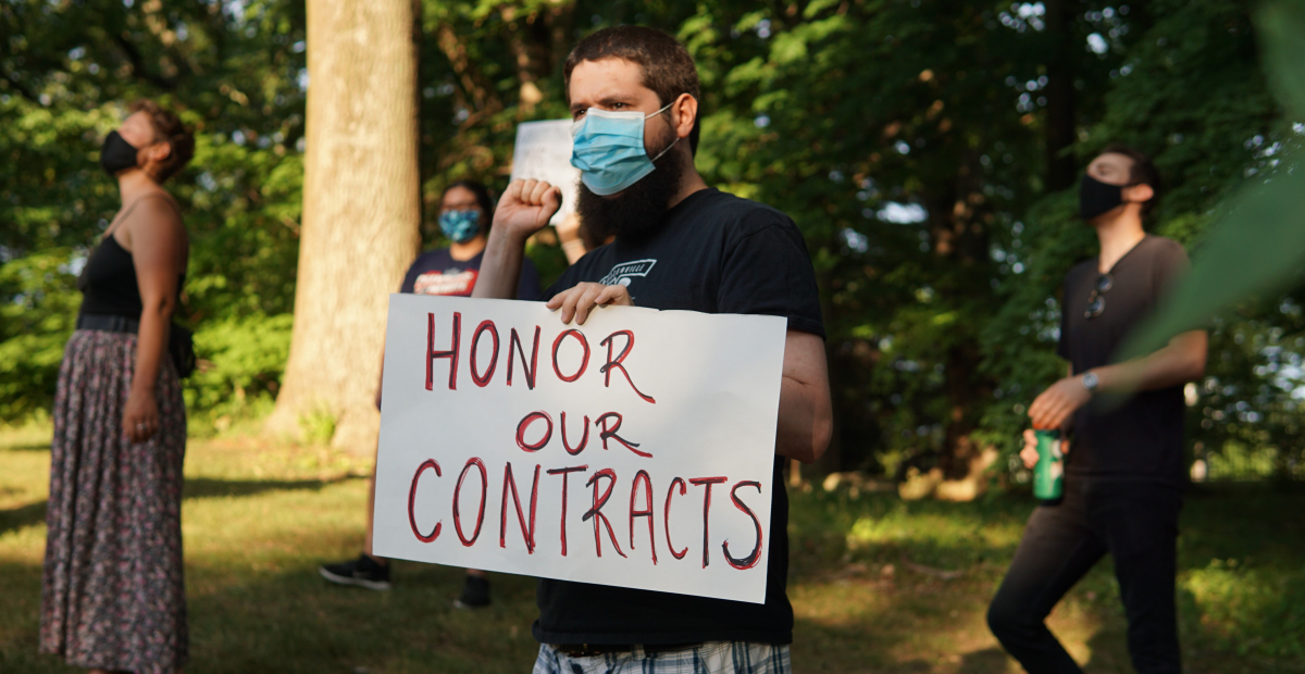 """Masked person holding sign """"Honor Our Contracts"""" in front of trees, other masked demonstrators"""
