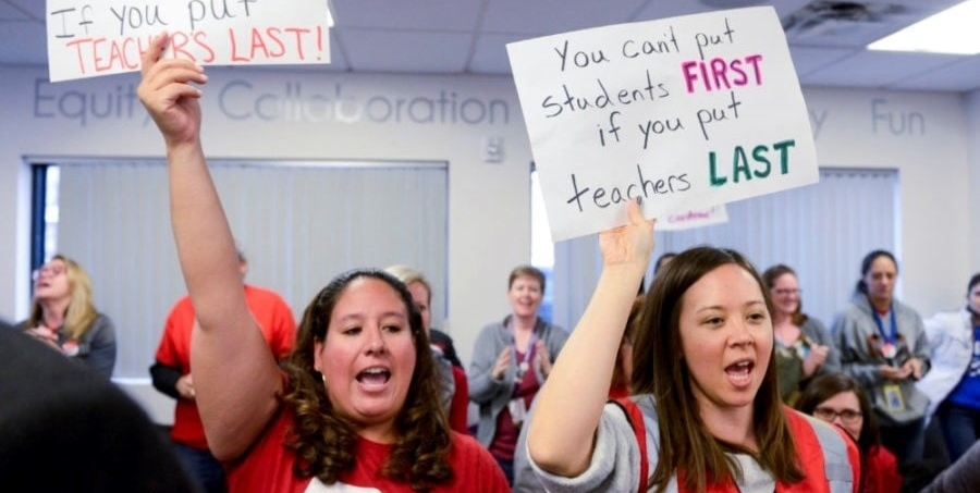 """Two teachers holding signs. Tiffany's sign says """"You can't put students first if you put teachers last."""""""
