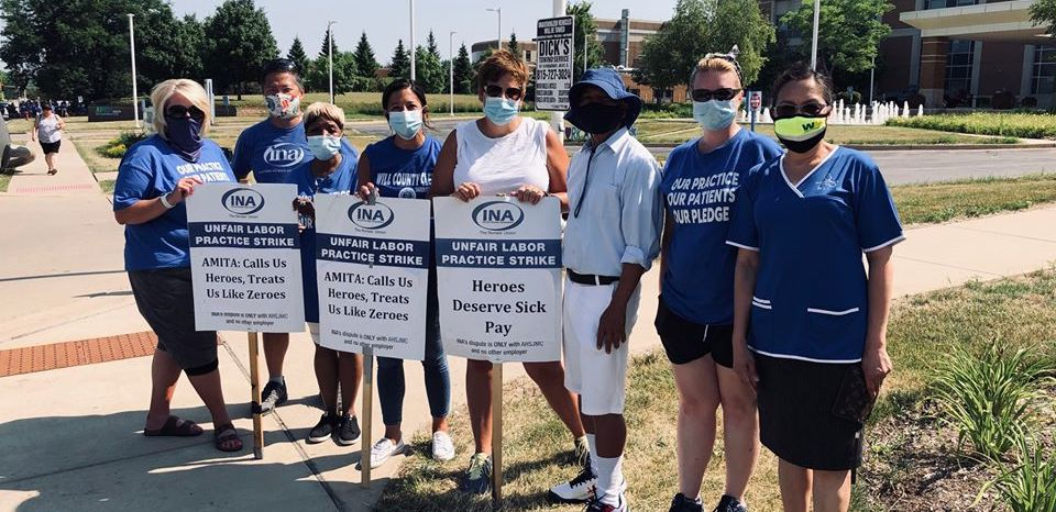 """Nurses hold picket signs that read """"AMITA: Calls Us Heroes, Treats Us Like Zeroes,"""" in front of St. Joseph Hospital."""