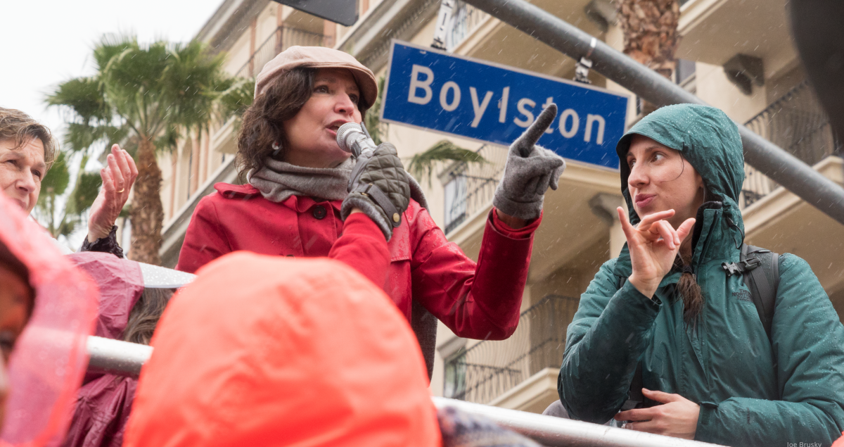 """A woman speaks at a strike rally while another woman interprets in sign language. Behind them is a palm tree, an apartment buidling or hotel, and a street sign """"Boylston"""""""