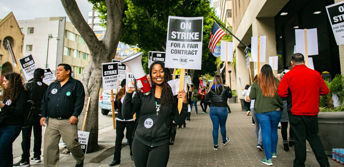 "A woman holds a bullhorn and a picket sign that says ""On Strike for a Fair Contract,"" surrounded by dozens of picketers holding similar signs and marching in a circle on the sidewalk."