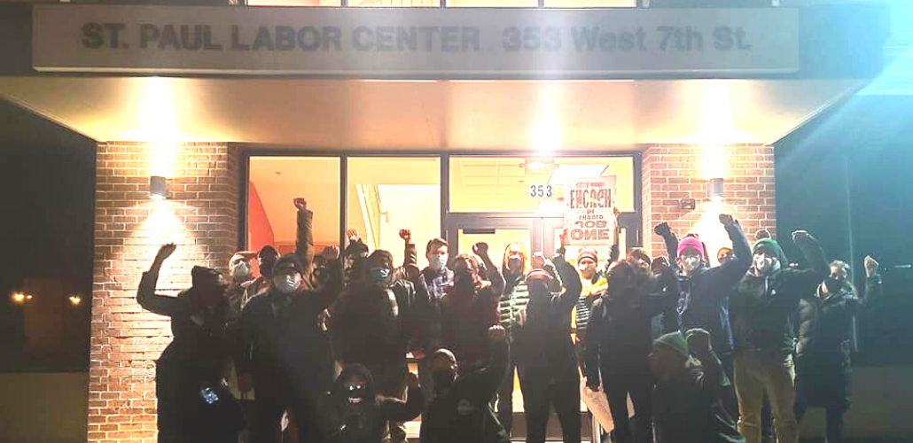 A group of people stands outside the St. Paul Labor Center, fists raised. It is dark out, and they are backlit.