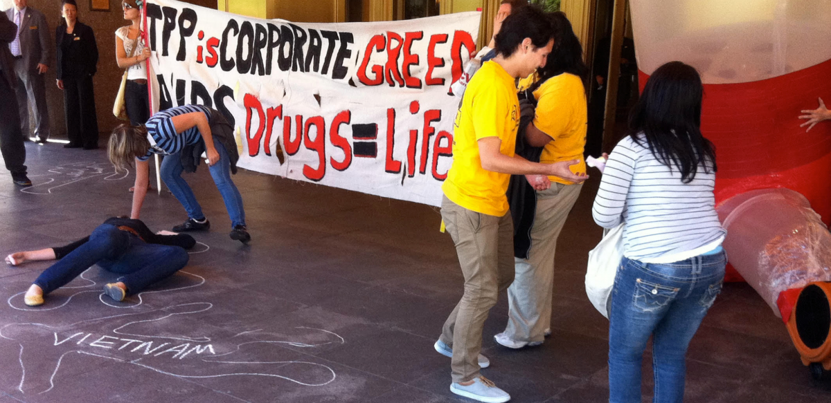 "Activists draw chaik outlines on the ground in front of a hotel entrance; one outline is labeled ""Vietnam."" Others hold a banner: ""TPP is corporate greed. AiDS drugs = life."""