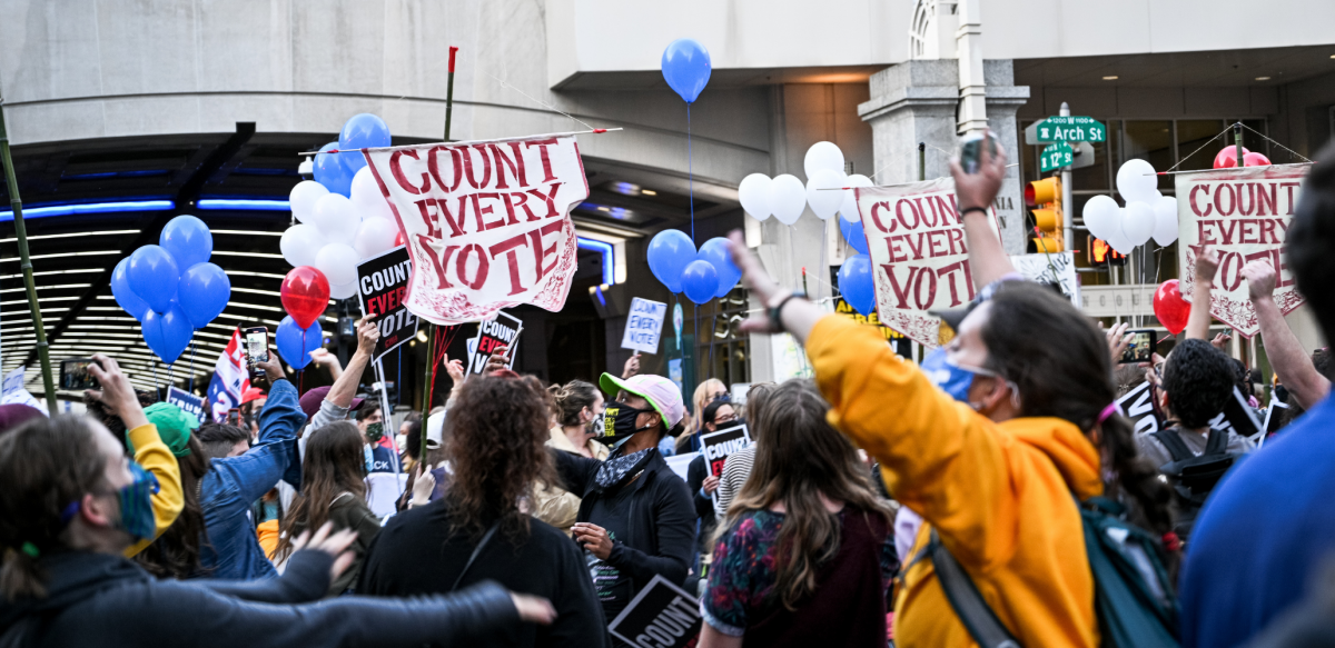 """Crowd with many """"count every vote"""" signs and balloons"""