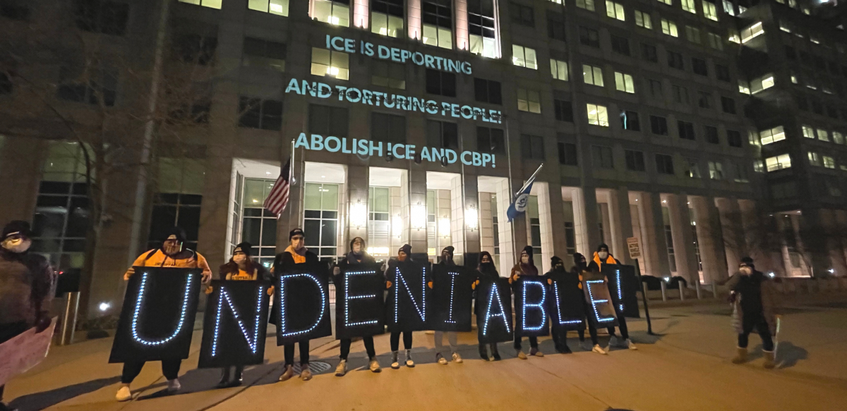 """People holding lit signs spelling out """"UNDENIABLE"""" stand in front of a building. On the building are projected the words: """"ICE IS DEPORTING AND TORTURING PEOPLE! ABOLISH ICE AND CBP!"""""""
