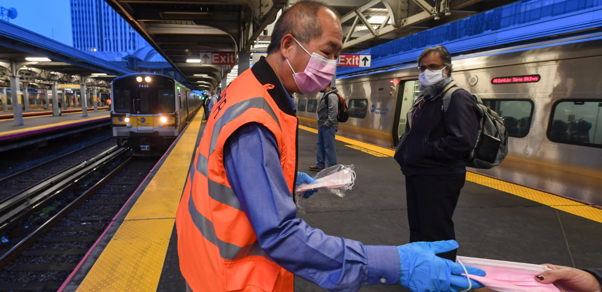 Man in orange vest hands out masks inside a train station