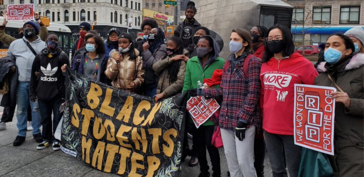 """A multiracial and multigenerational crowd rallies outside. Several help hold a large banner: """"BLACK STUDENTS MATTER."""" Others hold signs: """"WE WON'T DIE FOR THE DOE"""" and one wears a MORE T-shirt."""