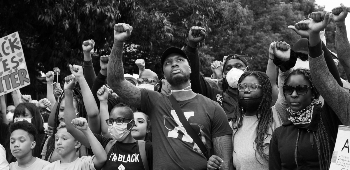 Black and white photo of a crowd people, mostly Black, various ages, all with fists raised in the air.