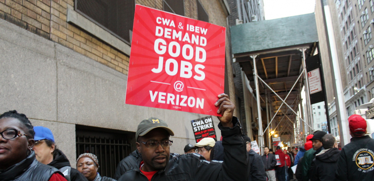 "A striking worker holds a sign saying ""CWA and IBEW Demand Good Jobs at Verizon"" during the 2016 Verizon strike."