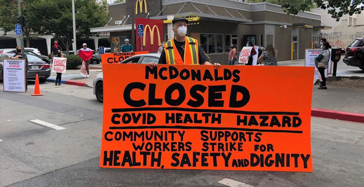 """masked worker in front of mcdonald's holds big orange sign: """"MCDONALD'S CLOSED, COVID HEALTH HAZARD, COMMUNITY SUPPORTS WORKERS STRIKE FOR HEALTH, SAFETY AND DIGNITY"""""""