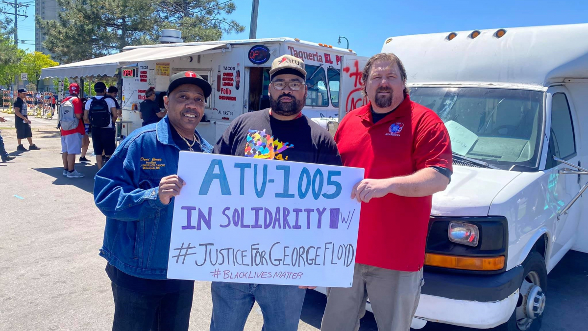 """Three men (two Black, one white) hold a sign: """"ATU-1005 in solidarity w/ #JusticeForGeorgeFloyd #BlackLivesMatter."""" Taco truck in background."""