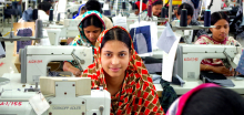 Bangladeshi garment worker at sewing machine looks up, sitting in factory
