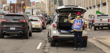 woman in front of the back of her car, trunk open, standing with a save usps sign.
